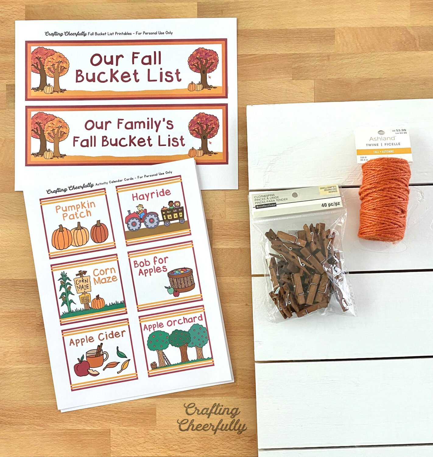 Supplies needed to make Fall Bucket List Sign lay on a table top including printables, board, twine and clothespins.
