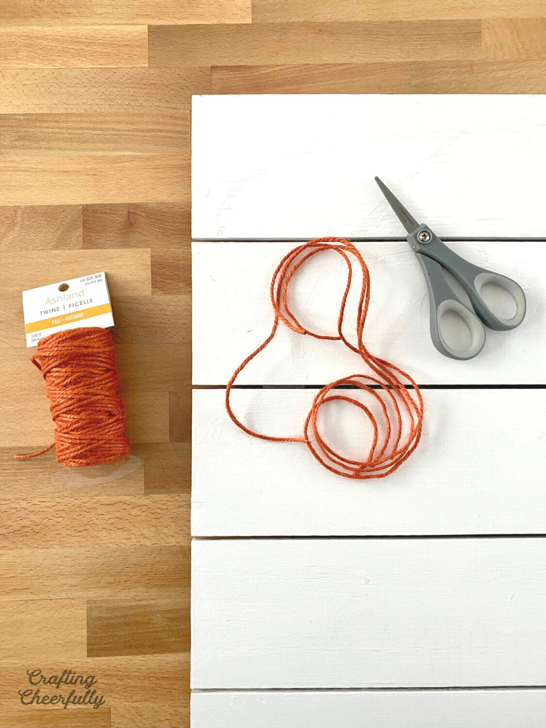 A white wooden board, a roll of orange twine and a scissors lays on a table.