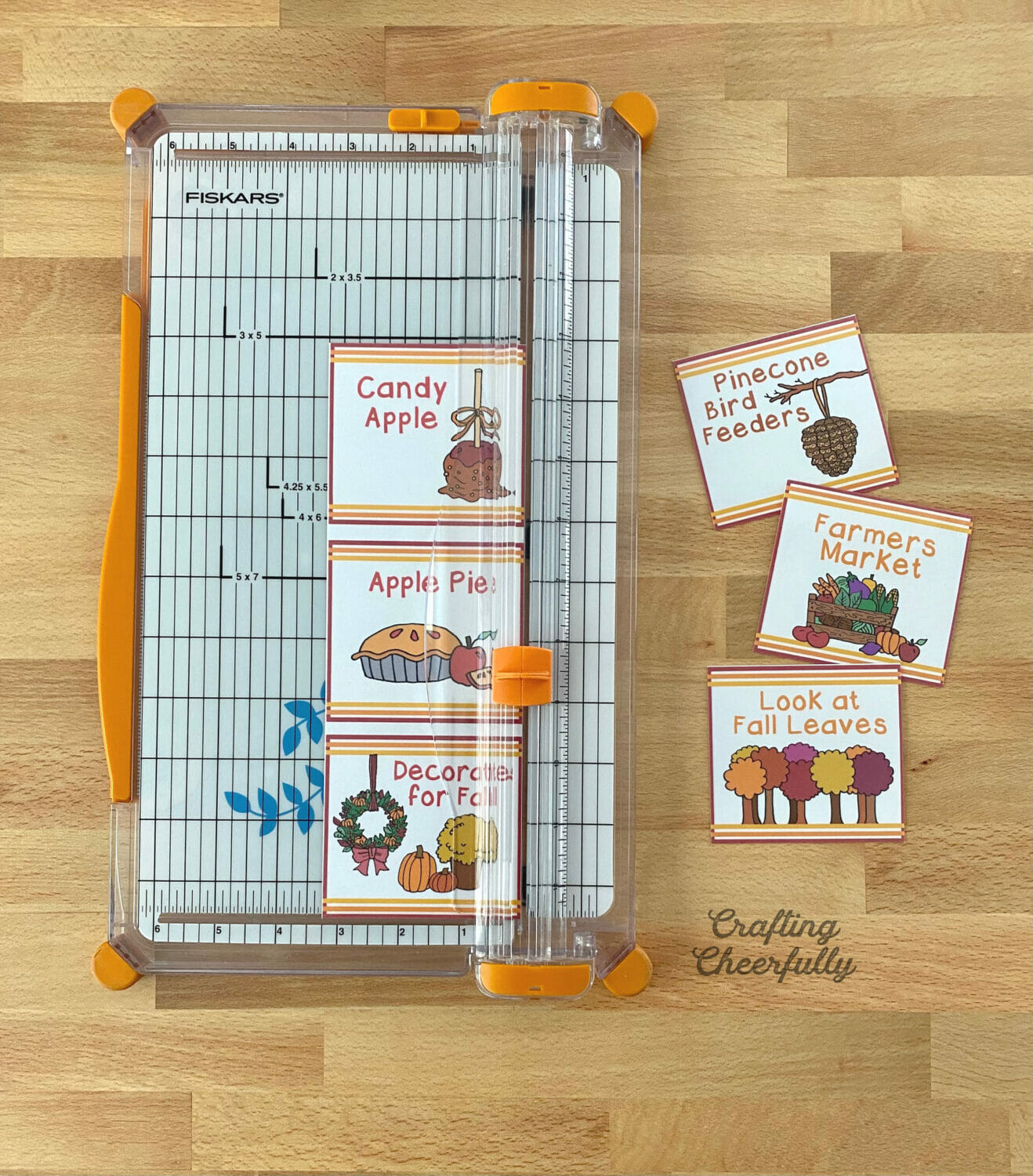 Paper trimmer cutting out fall bucket list cards lays on a table top.