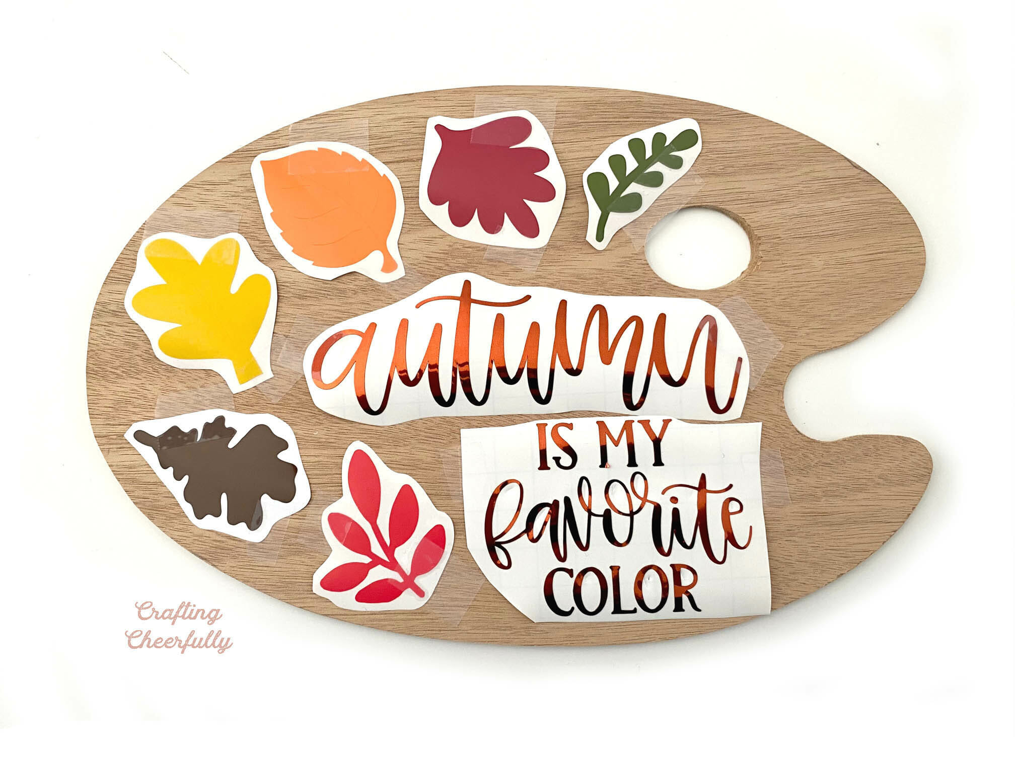 Wooden paint palette with cut out vinyl leaves laying on top of it.