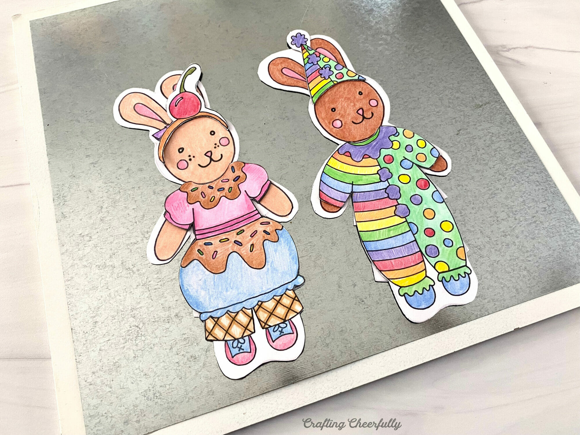 Bunny paper dolls dressed in Halloween costumes are stuck to a magnetic dry erase board laying on a purple surface.