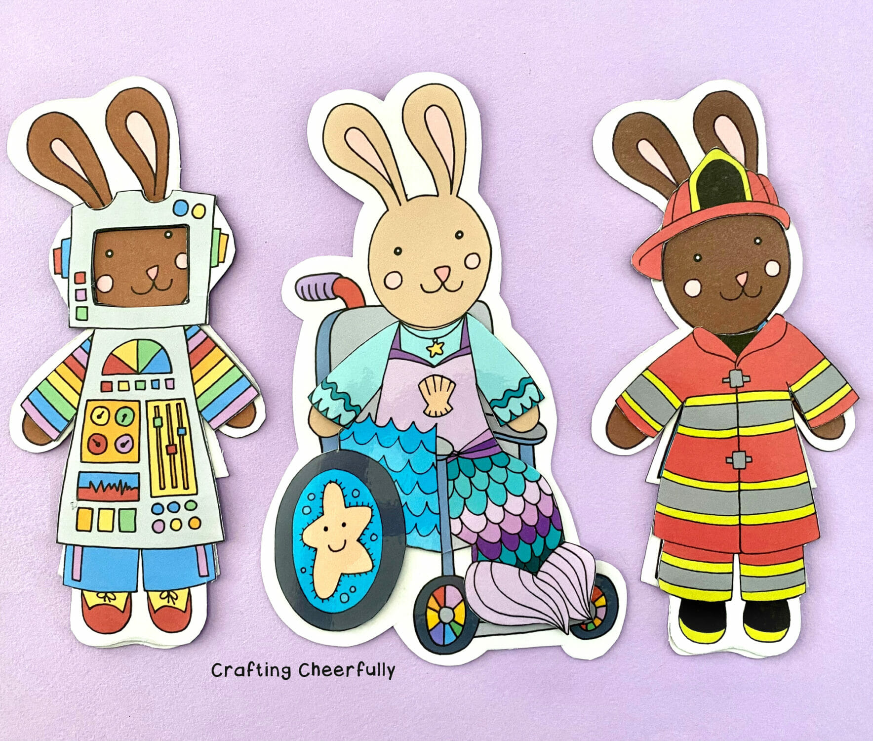 Bunny paper dolls dressed in Halloween costumes lay on a purple surface.