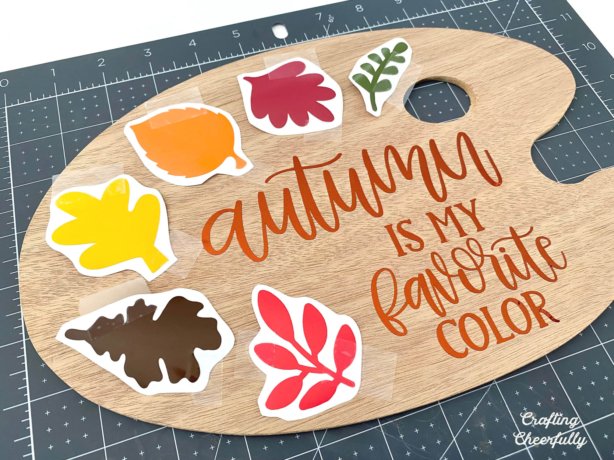 """Autumn sign in the shape of a paint palette with vinyl leaves arranged on them and the saying """"Autumn is my Favorite Color"""""""