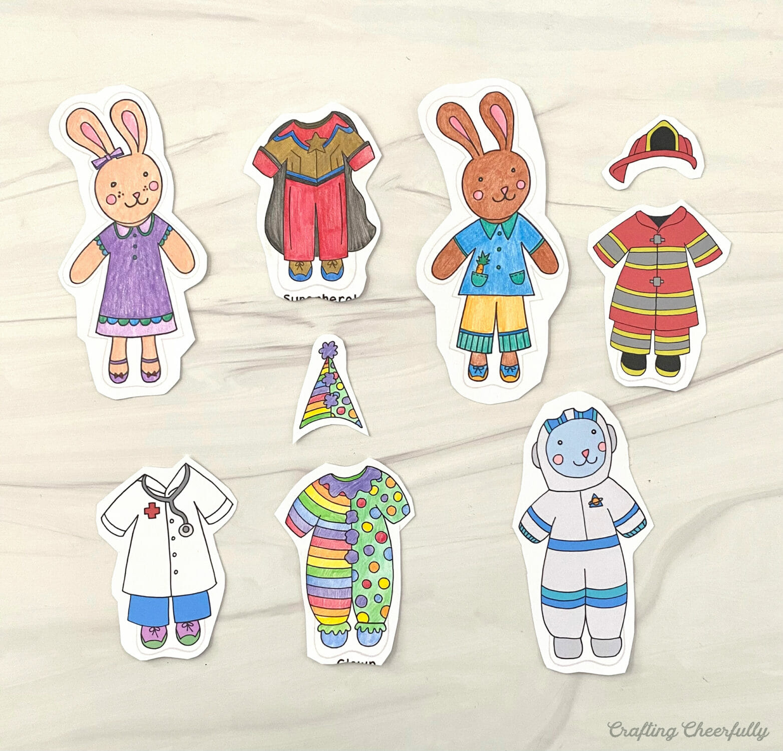 Bunny paper dolls partially cut out lay on a table.
