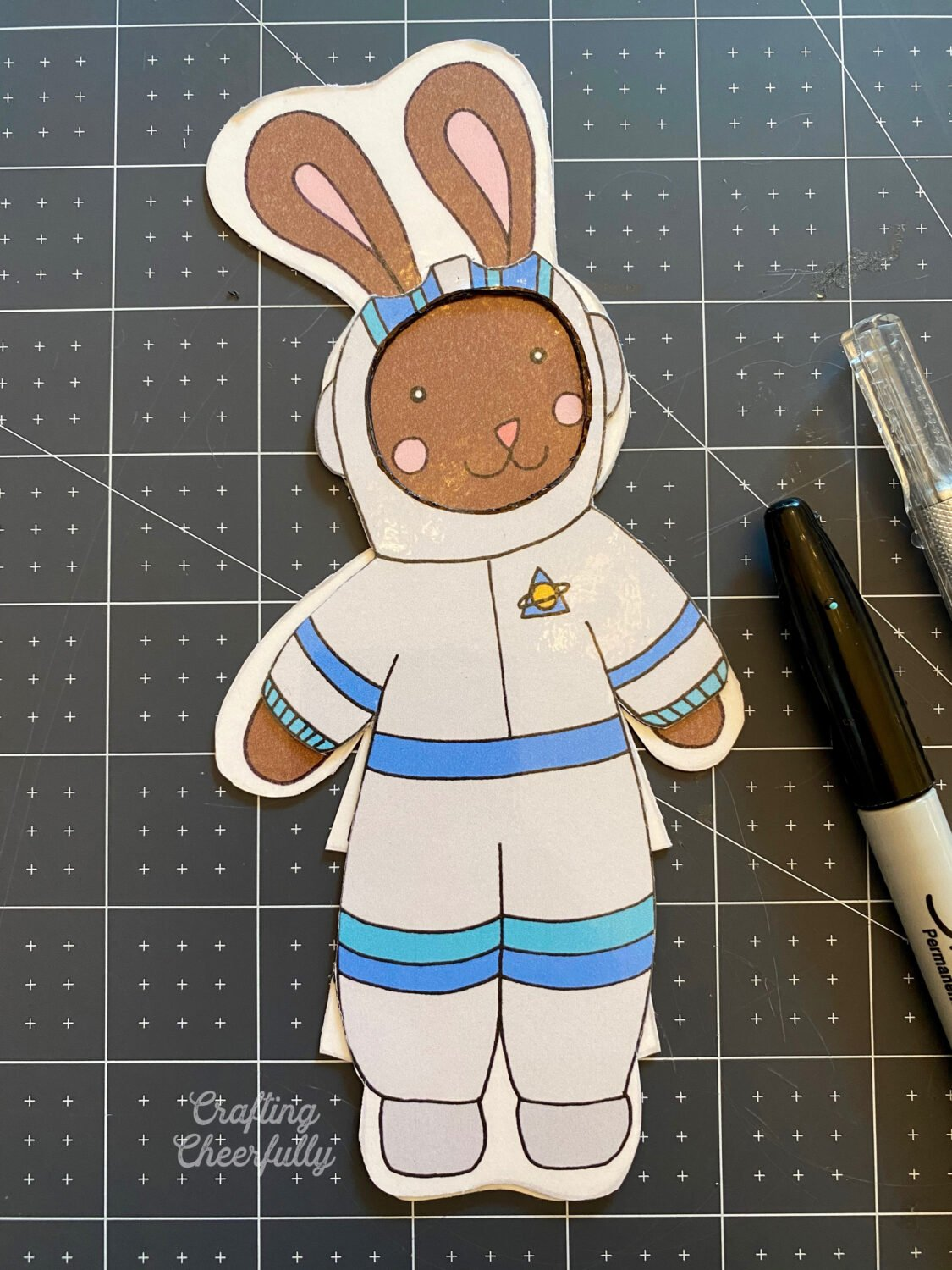 A bunny dressed in a halloween astronaut lays on a black mat.