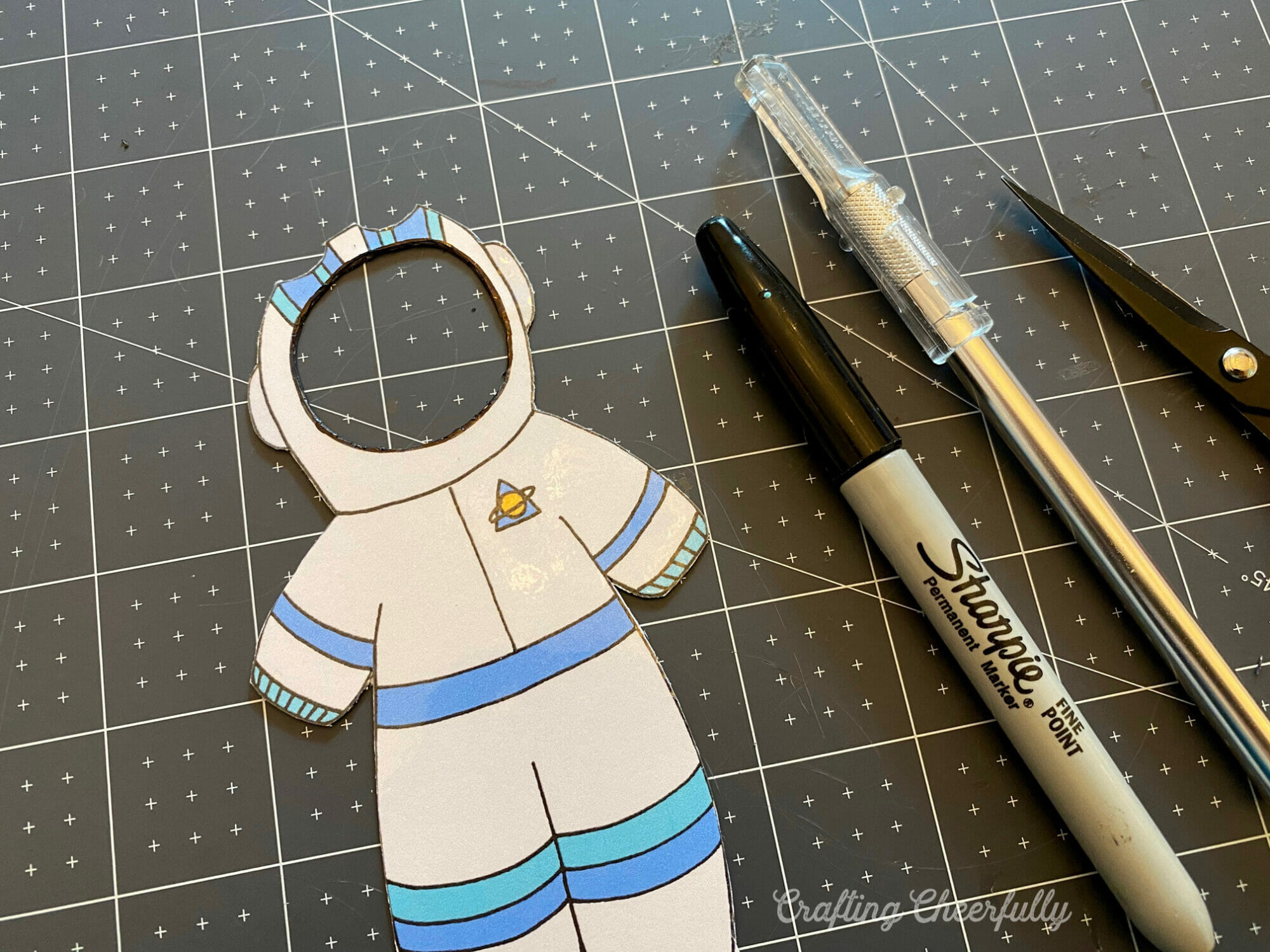 An paper astronaut costume is cut out carefully and lays on a black mat.
