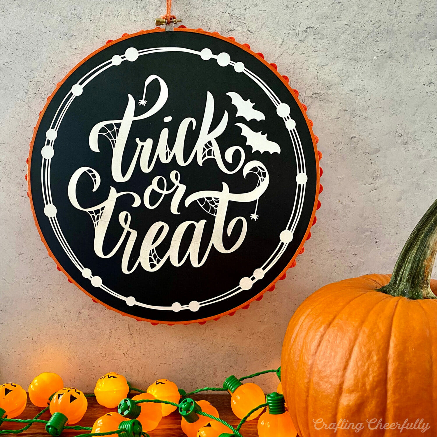 Halloween embroidery hoop hangs on a wall with a pumpkin and pumpkin lights underneath it on a tabletop.