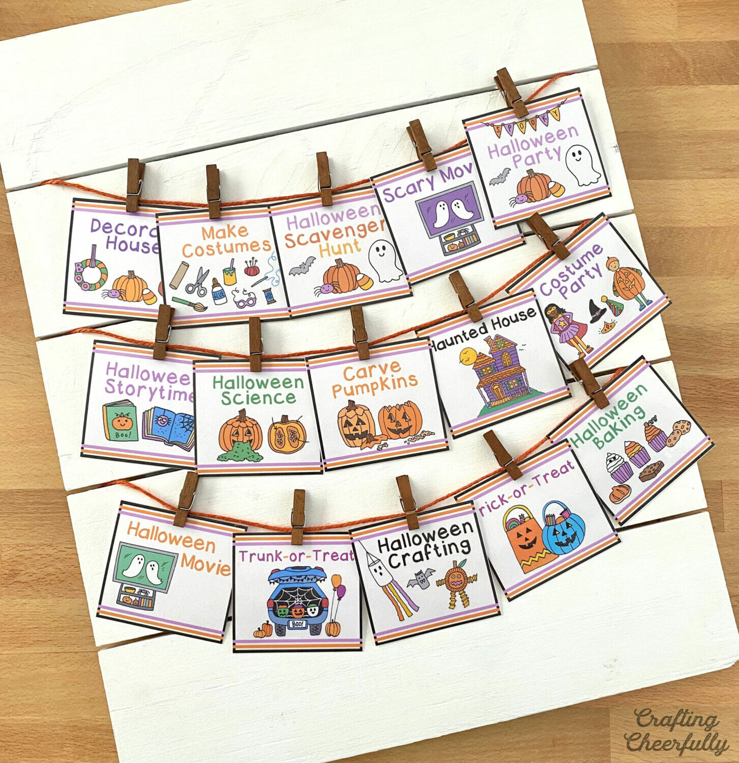 A row of Halloween bucket list cards are hung on a white wooden board using orange twine and mini clothespins.