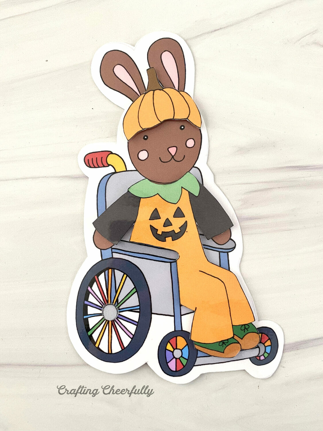A paper doll bunny using a wheelchair is dressed in a pumpkin costume for Halloween.