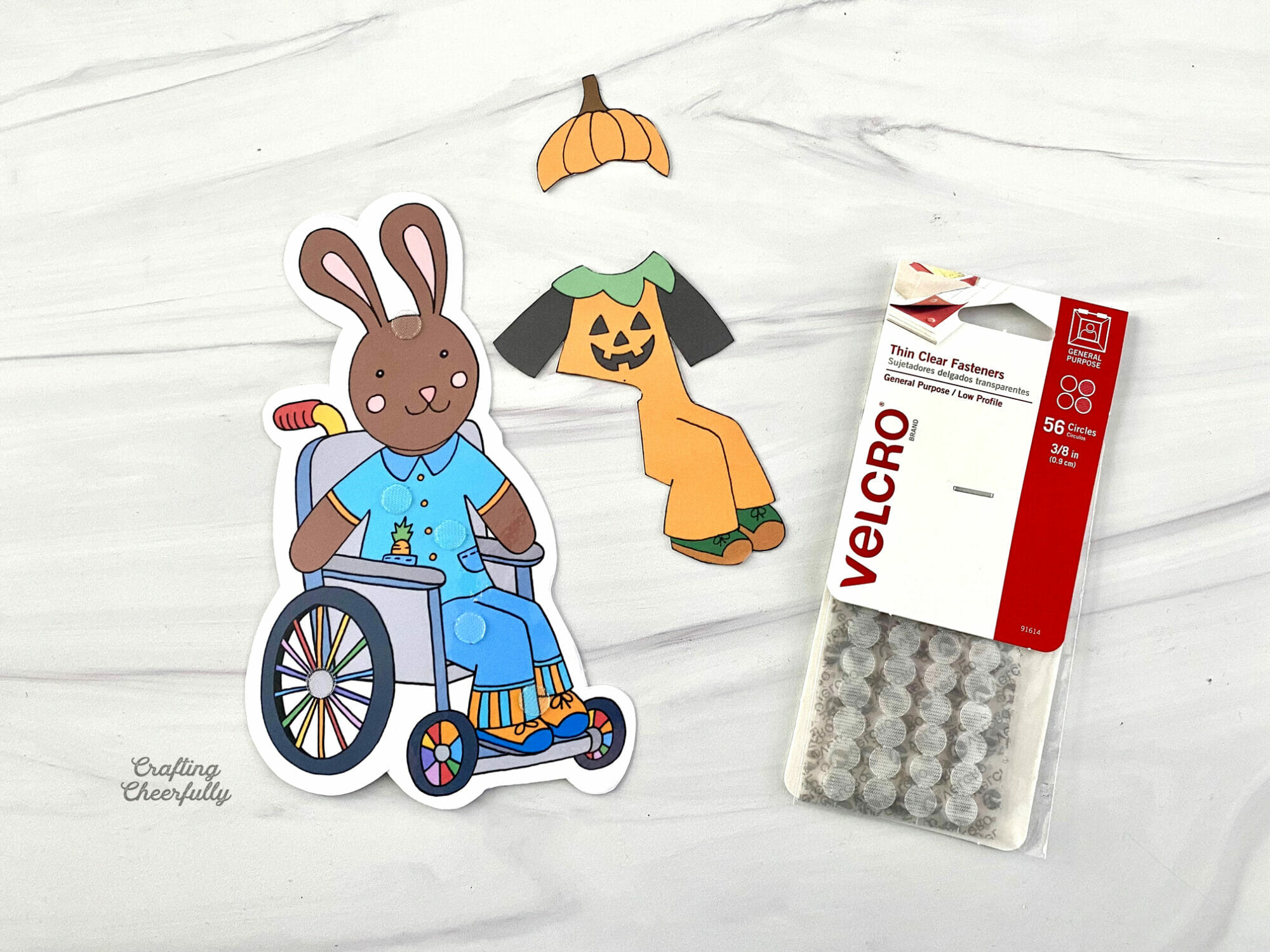 A paper brown bunny sitting in a wheelchair lays next to a paper pumpkin costume.