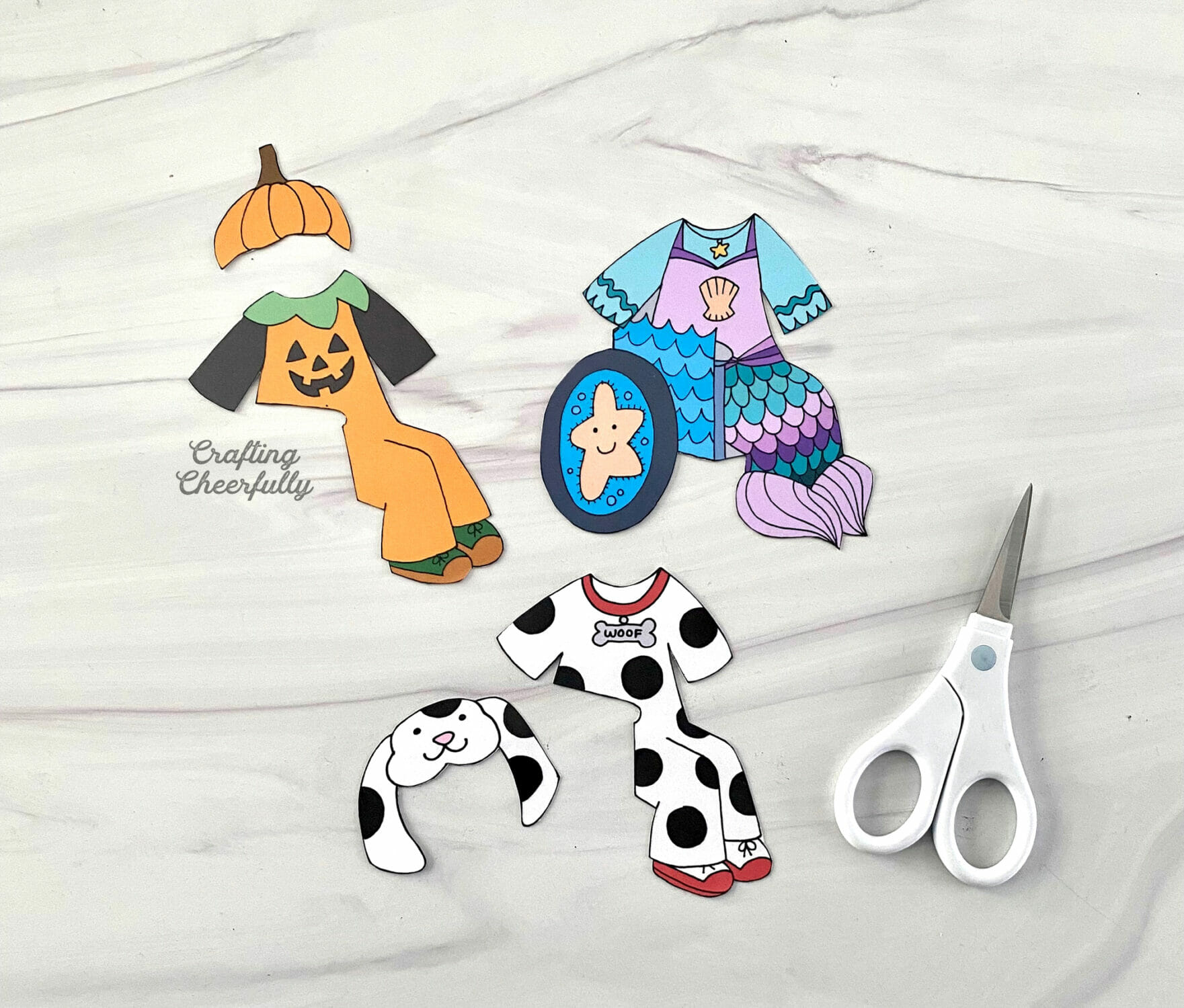Paper costumes lay on a table next to a white scissors.