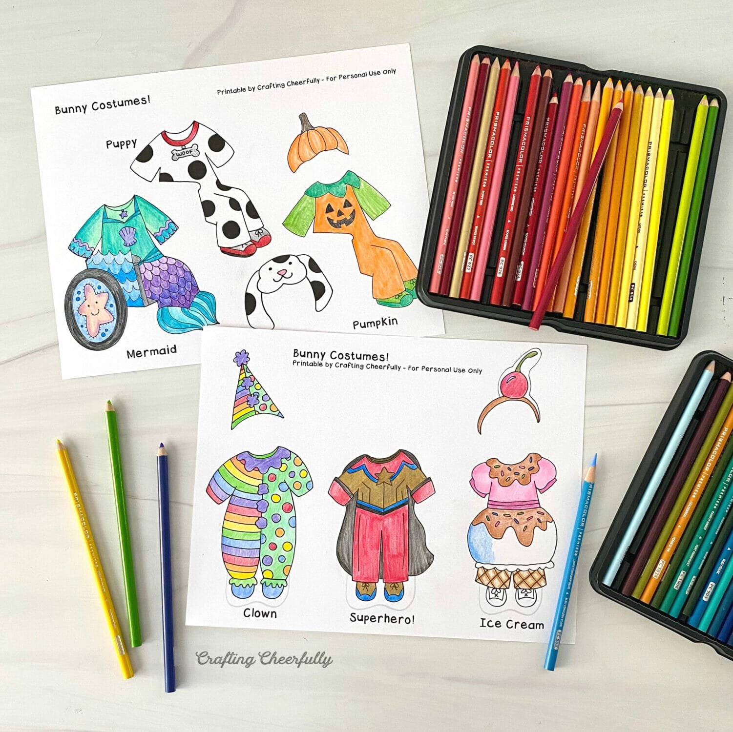 Coloring sheets with Halloween costumes lay on a table top next to trays of colored pencils.