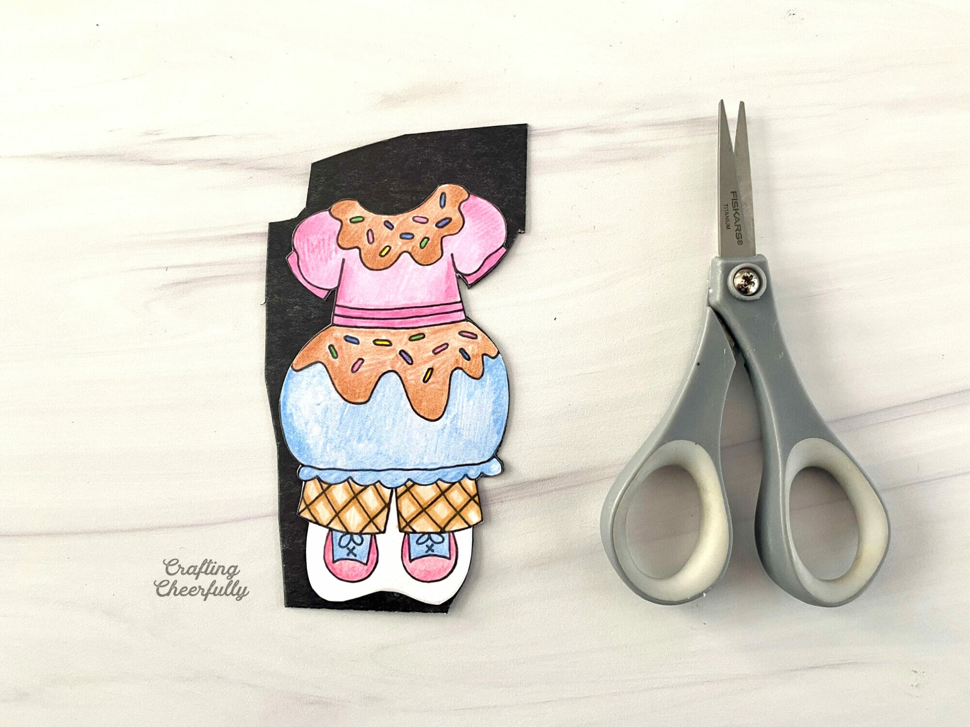 An ice cream costume is colored in on a piece of paper and adhered to a piece of magnet sheet.
