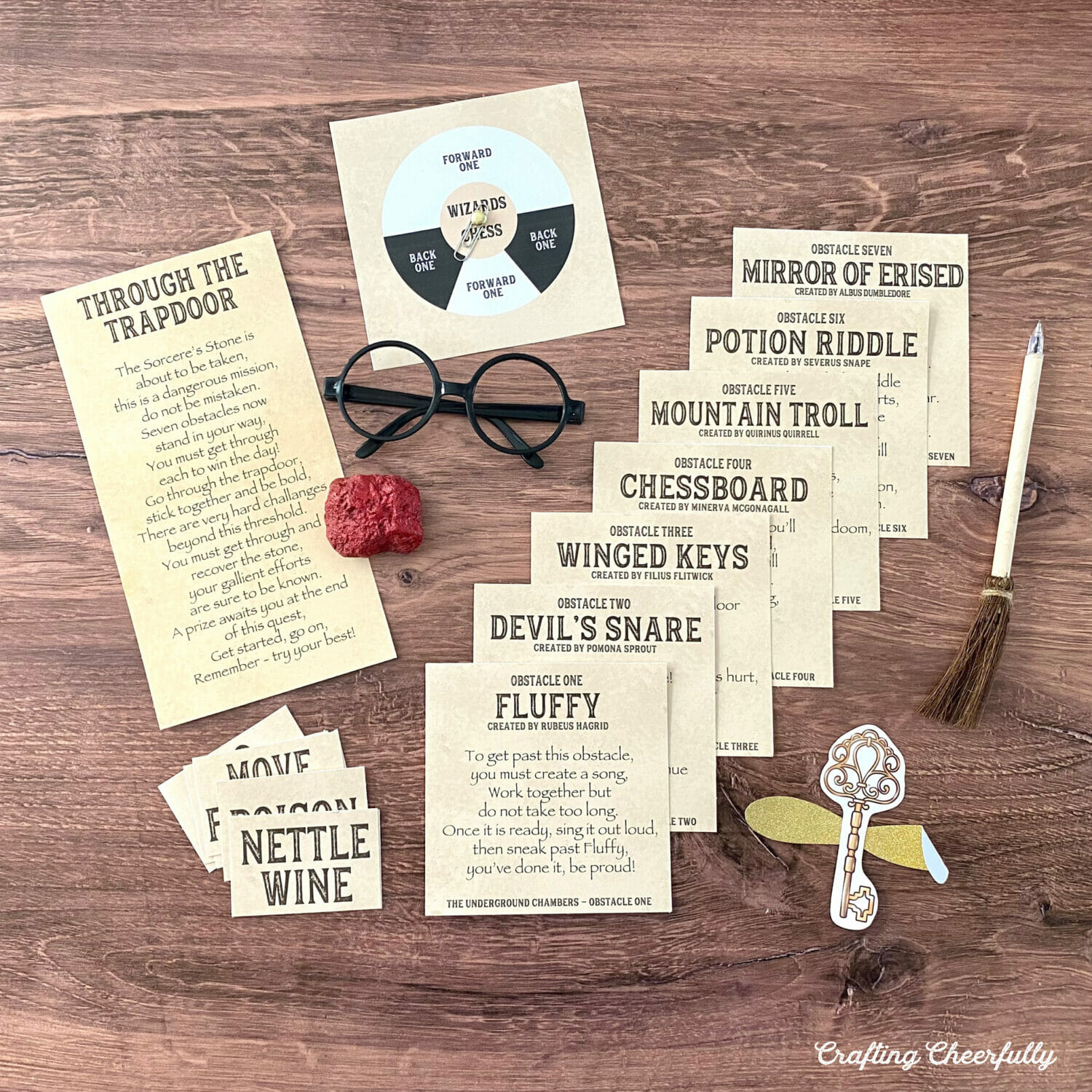 Harry Potter printable game cards lay on a table with a red sorcerer's stone, black glasses and a broom pen.
