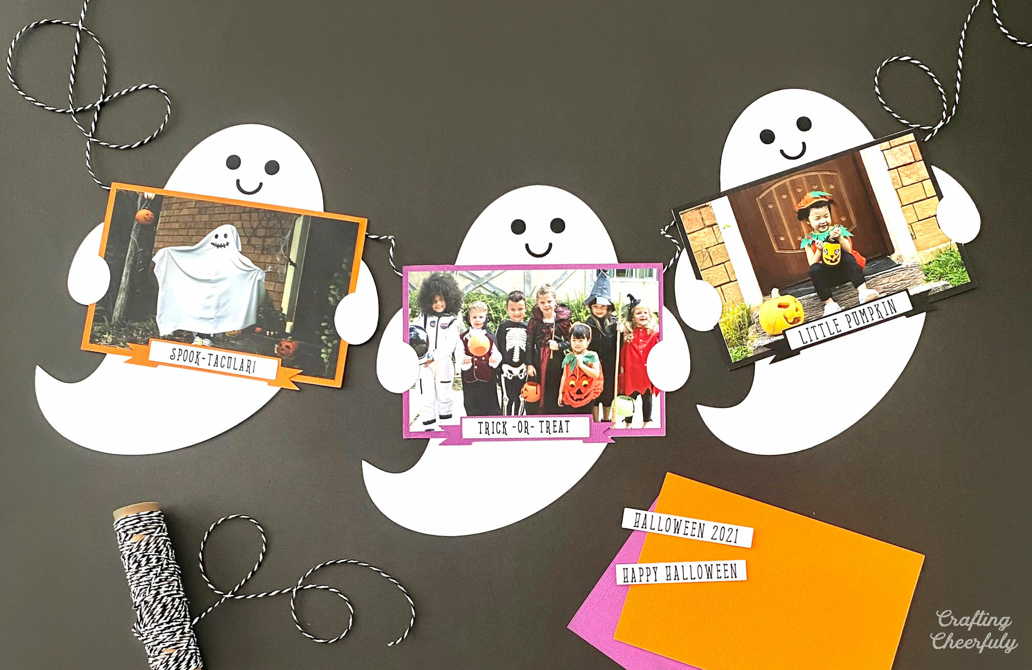 Ghost banner made from paper ghosts holding photos lays on a black table with craft supplies around it.
