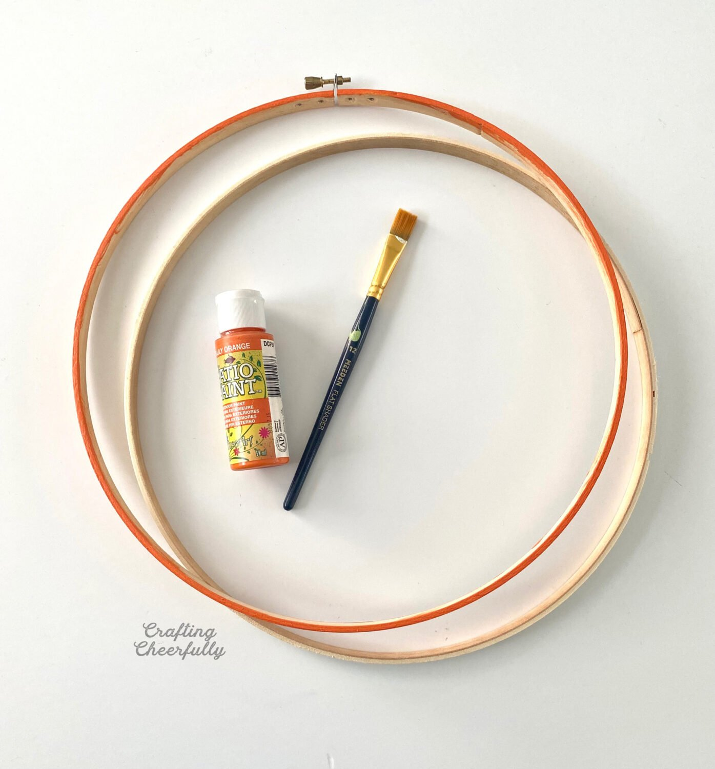 Embroidery hoop, with the top hoop painted orange, lay on a table next to a tube of orange paint and a paintbrush.