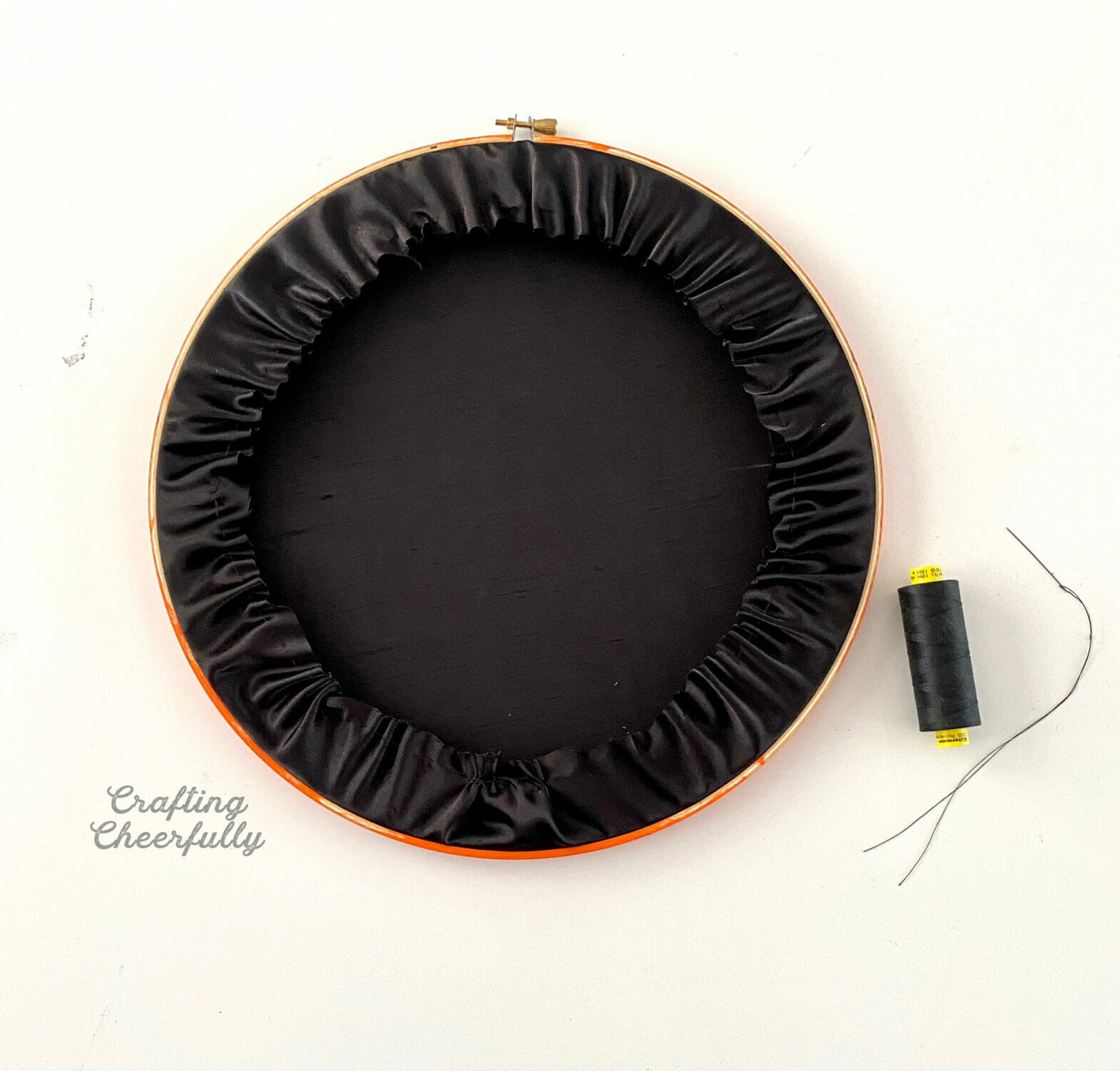 The back of the embroidery hoop showing the black fabric being gathered in.