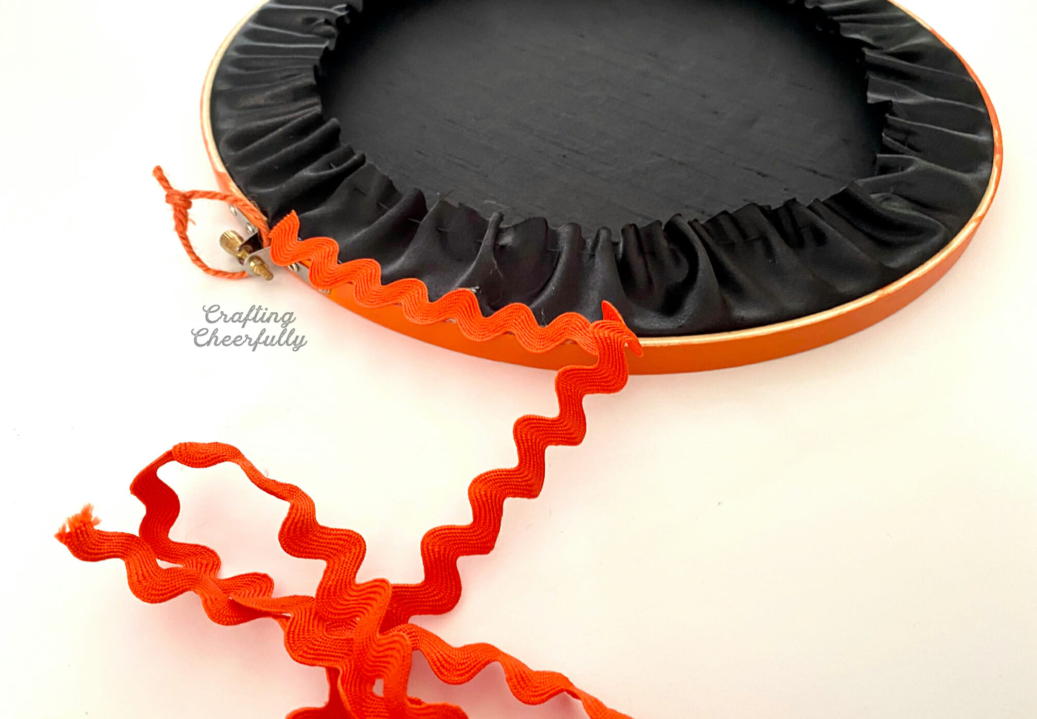 Orange ric rac is applied to the outer edge of an embroidery hoop.