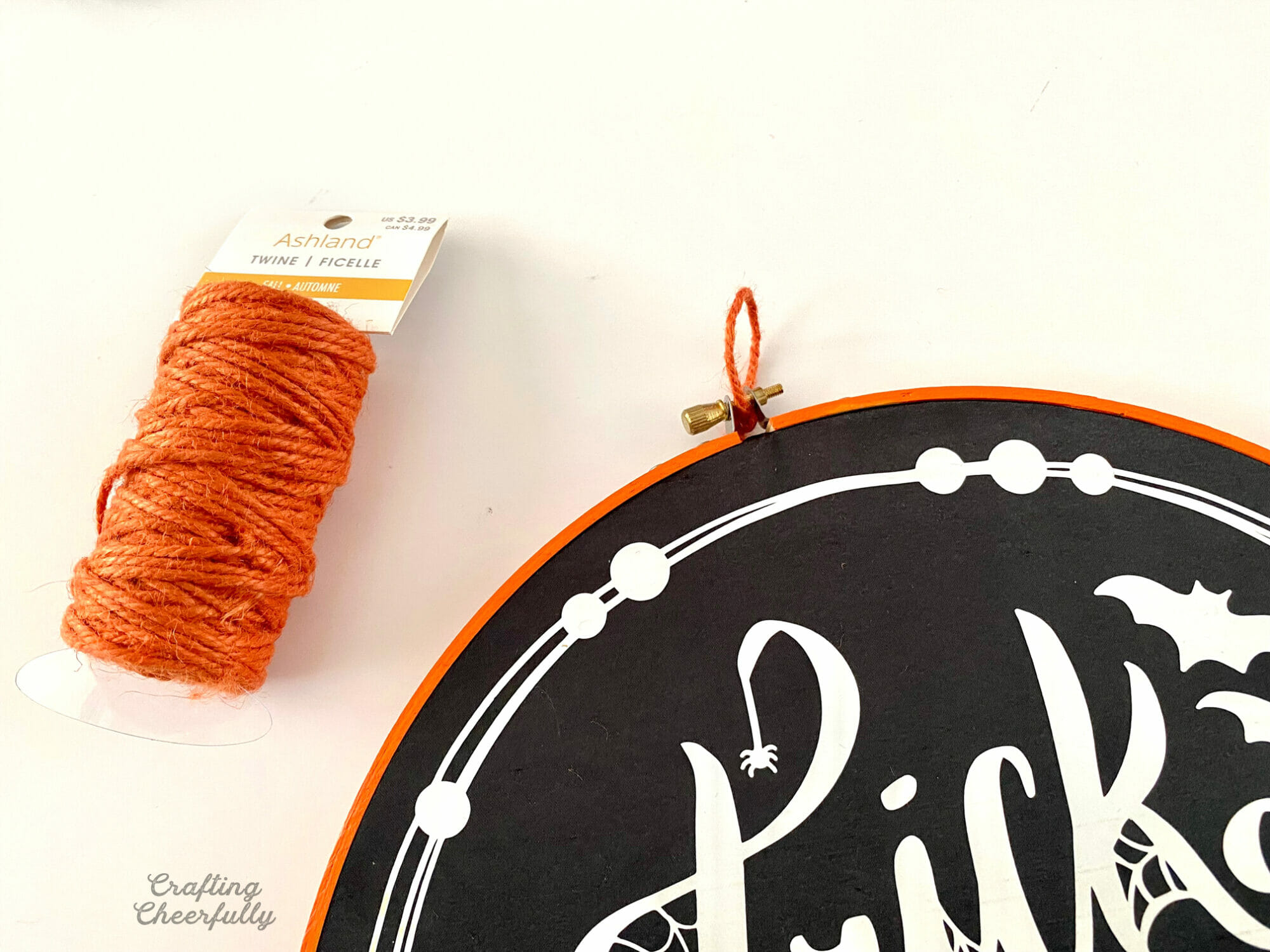A loop of orange twine is added to the top of the embroidery hoop.