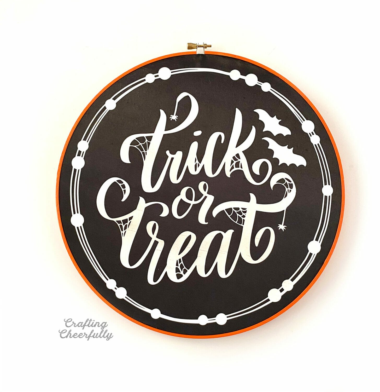 """Embroidery hoop painted orange with """"Trick or Treat"""" written in glow in the dark HTV on black fabric."""