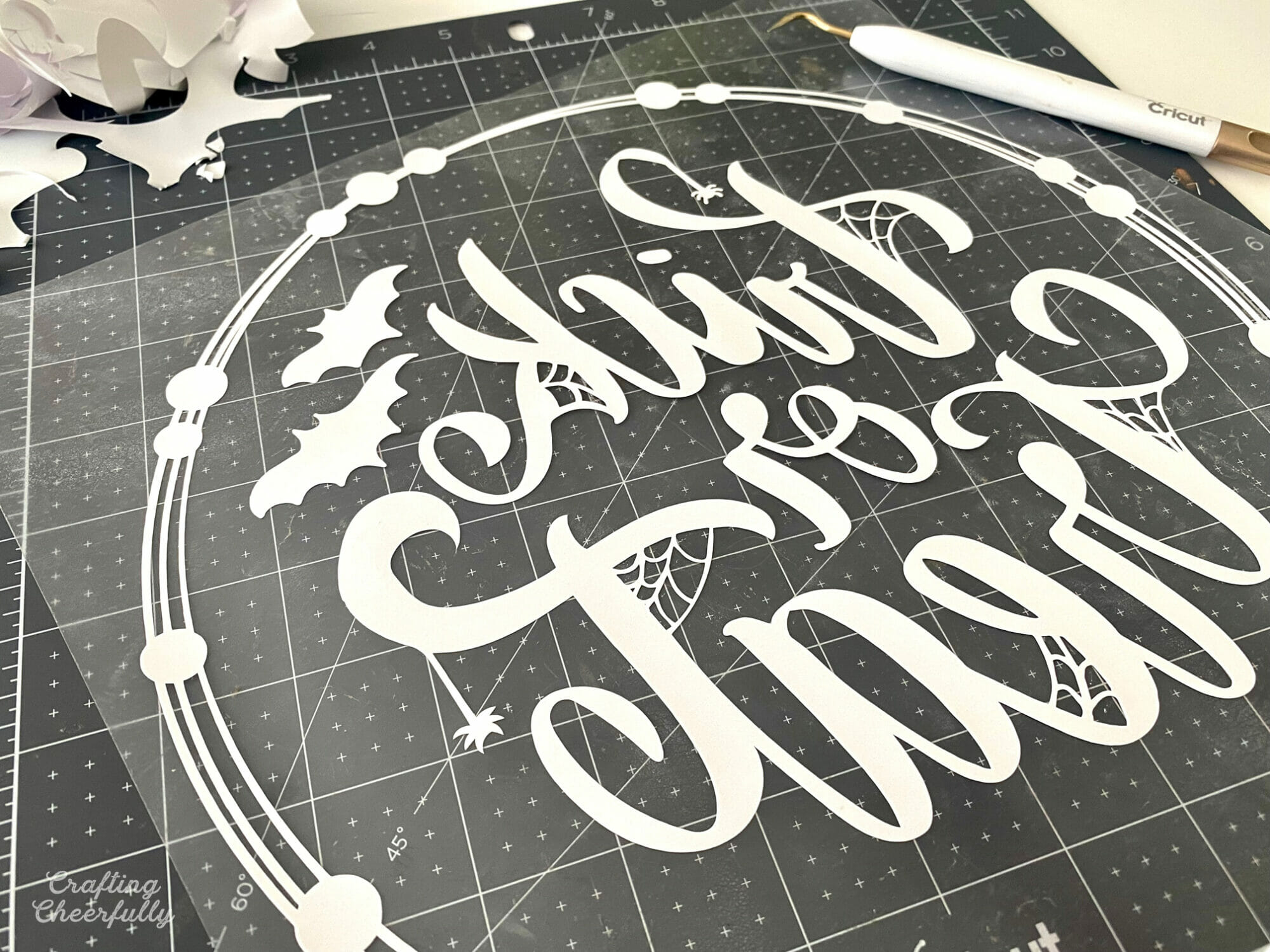 HTV design is weeded on a black cutting mat.