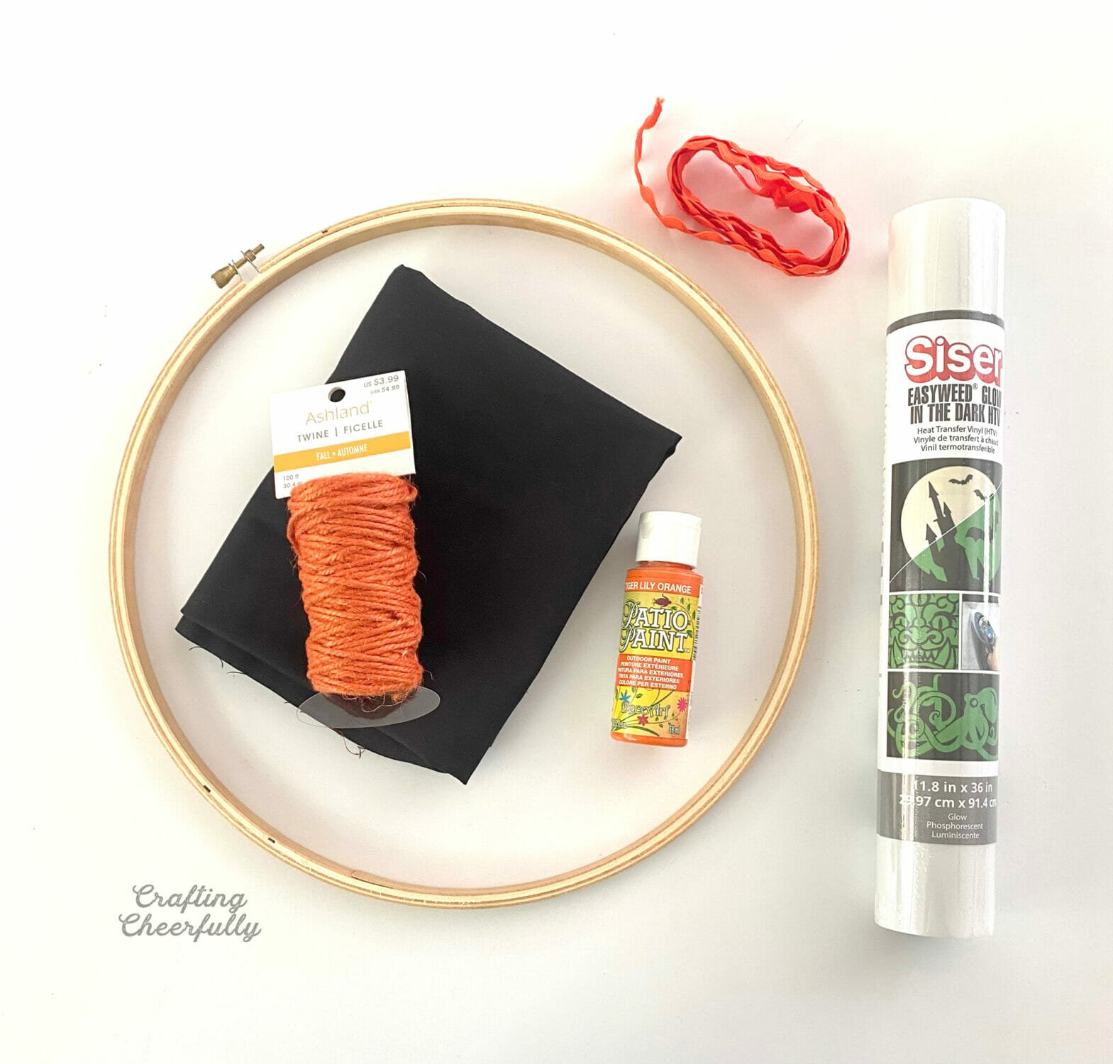 Supplied needed for the Halloween hoop wreath including an embroidery hoop black, fabric, orange paint, and a roll of glow-in-the-dark heat transfer vinyl lay on a white table top.