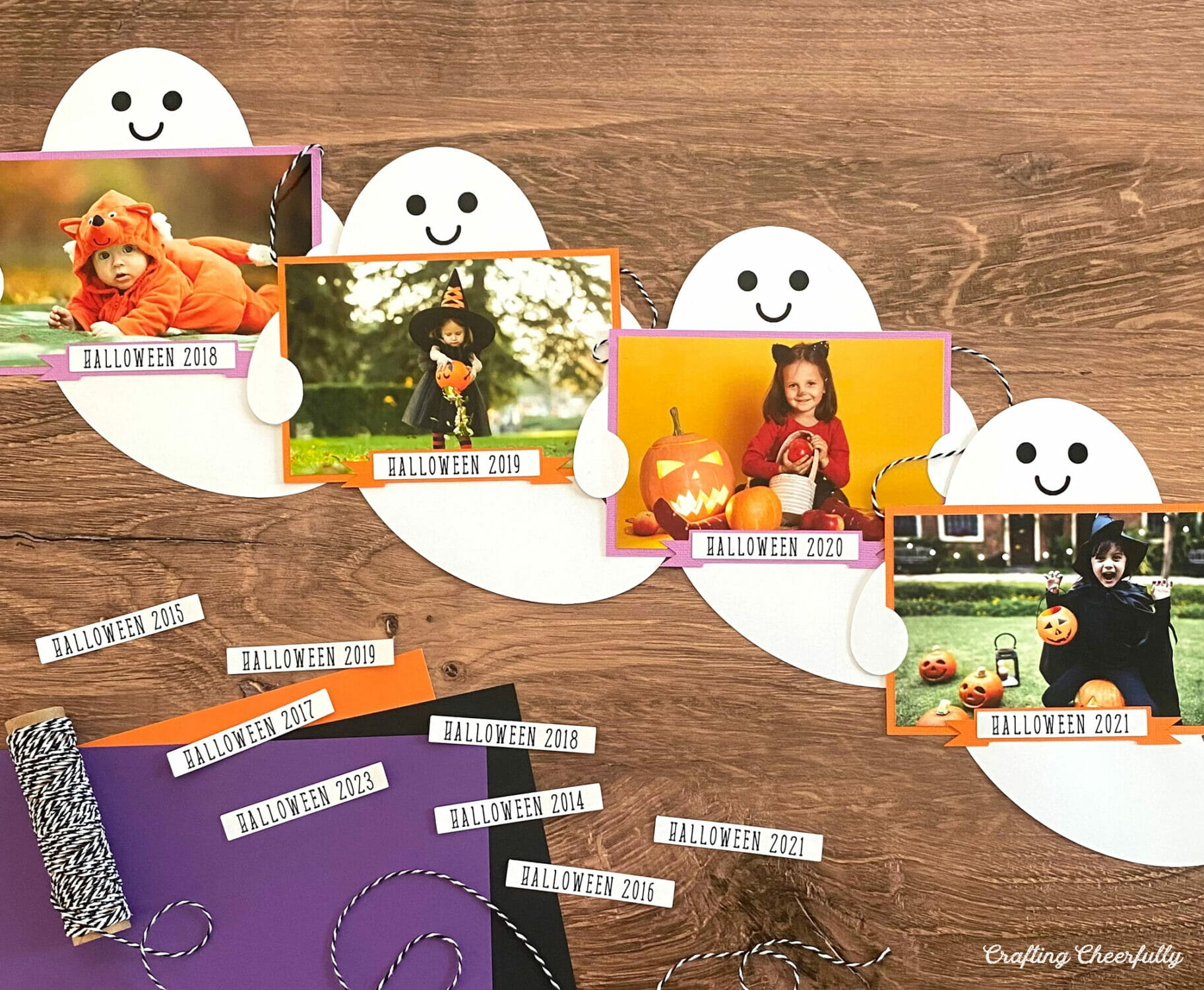 Halloween ghost banner with cute paper ghosts holding Halloween photos.