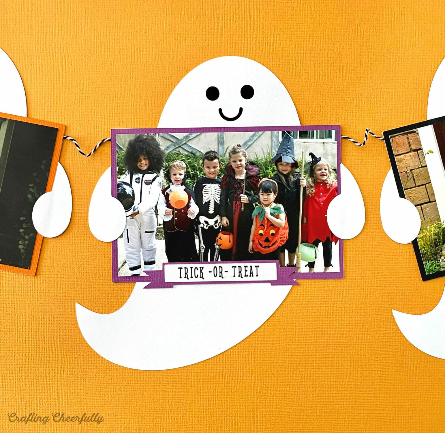 Paper ghost pennant holding a Halloween photo.