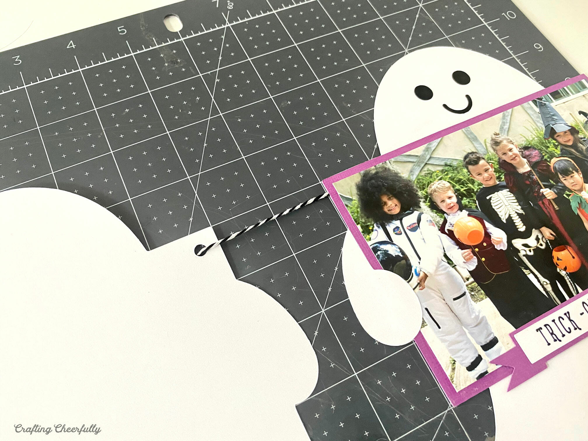Two paper ghosts connect by black and white Baker's twine to form a banner lay on a black cutting mat.