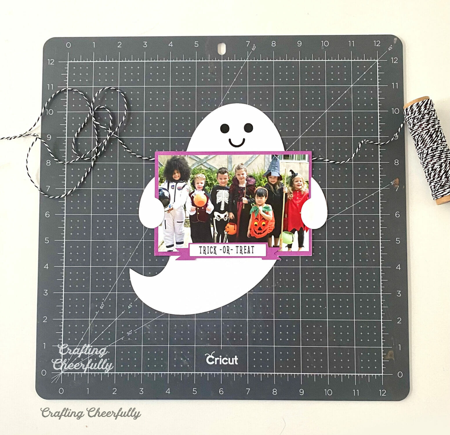 """Paper ghost holding a photo of kids in costume lays on a black cutting mat with a label that reads """"Trick or Treat""""."""
