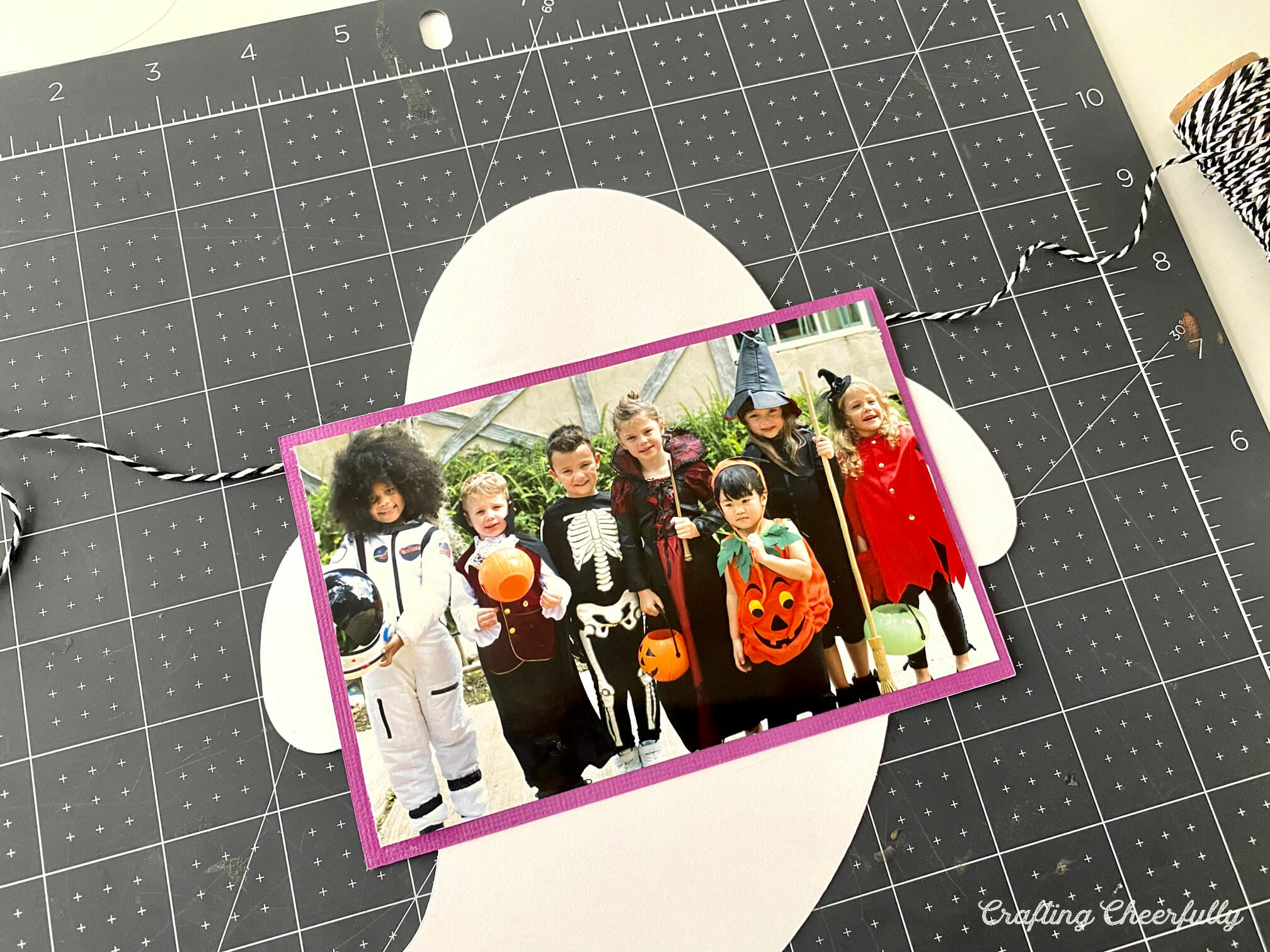 Ghost paper banner pennant lays on a black mat with a picture of kids in Holloween costume.