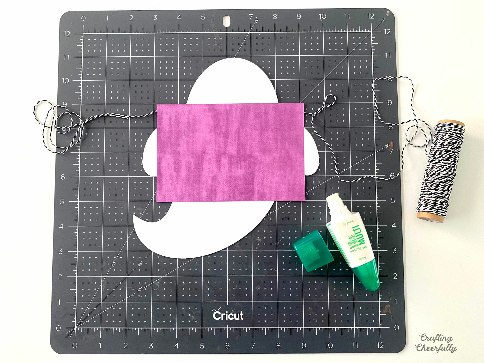 A white paper ghost holding a purple piece of paper in the shape of a rectangle sits on a black cutting mask next to a glue pen.