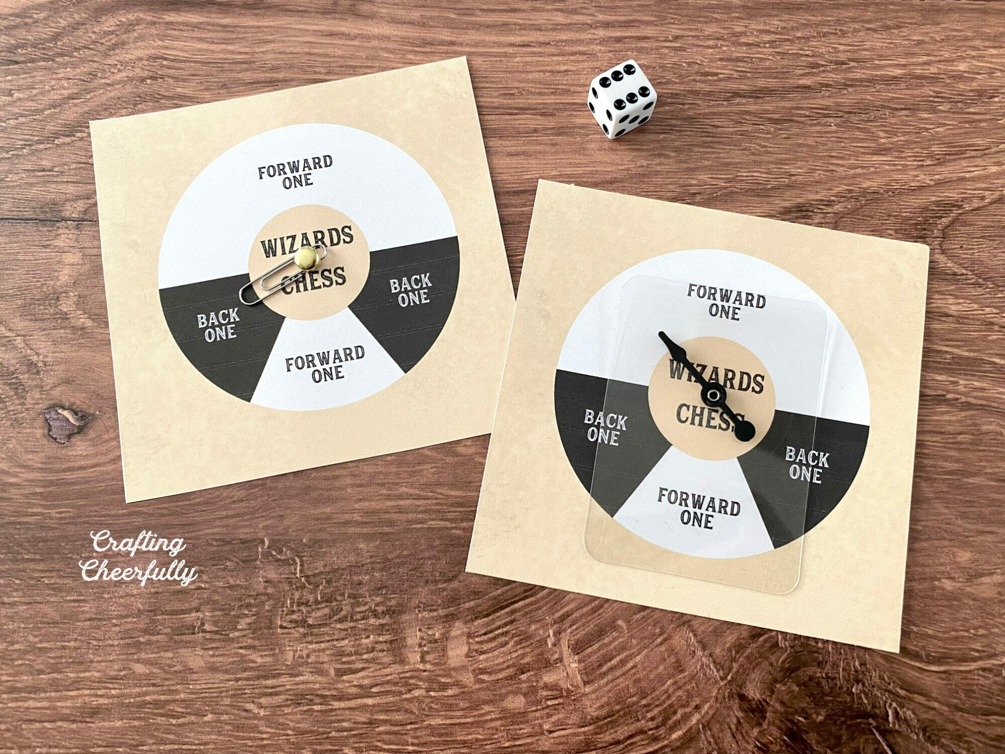 Two printable game spinner lay next to a dice on a wooden table.