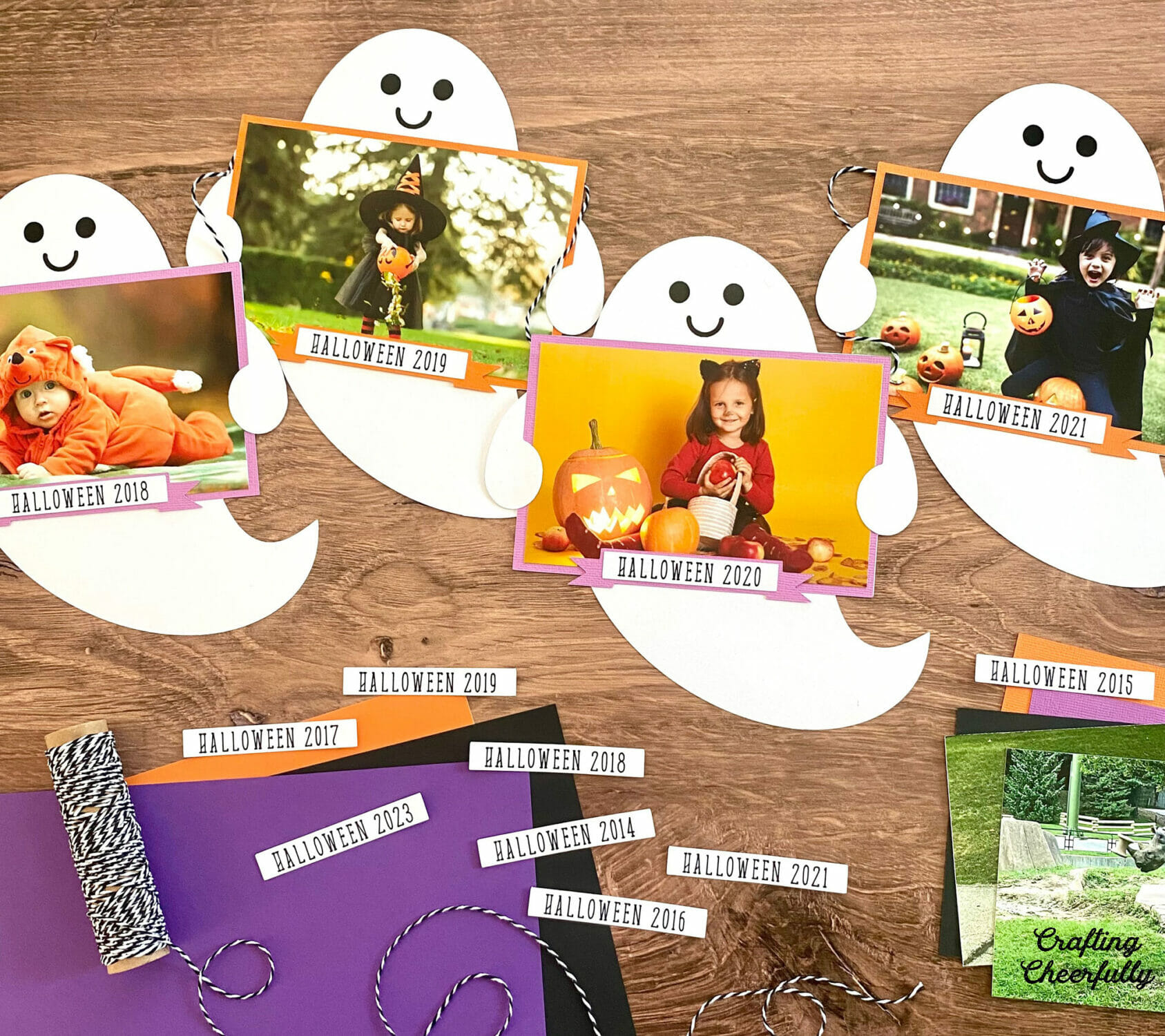 Paper Ghost Banner with ghosts holding photos and the year labeled.
