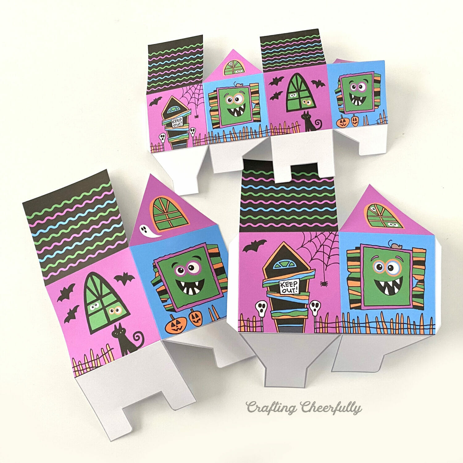 Cut out monster treat box printables folded along their score lines lay on a white table.