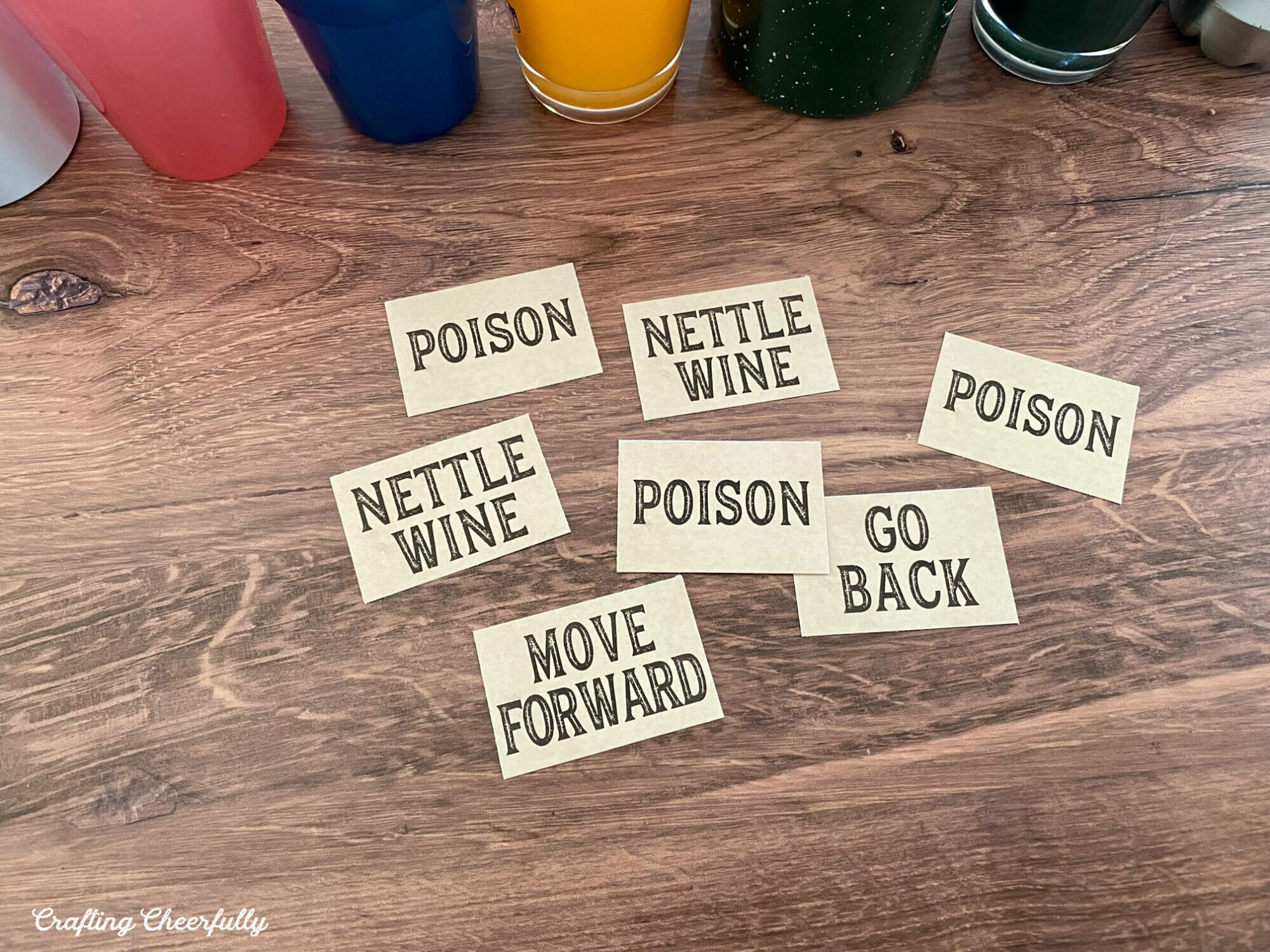 Small game cards that read Nettle Wine, Poison, Go Back and Move Forward lay on a table in front of cups.