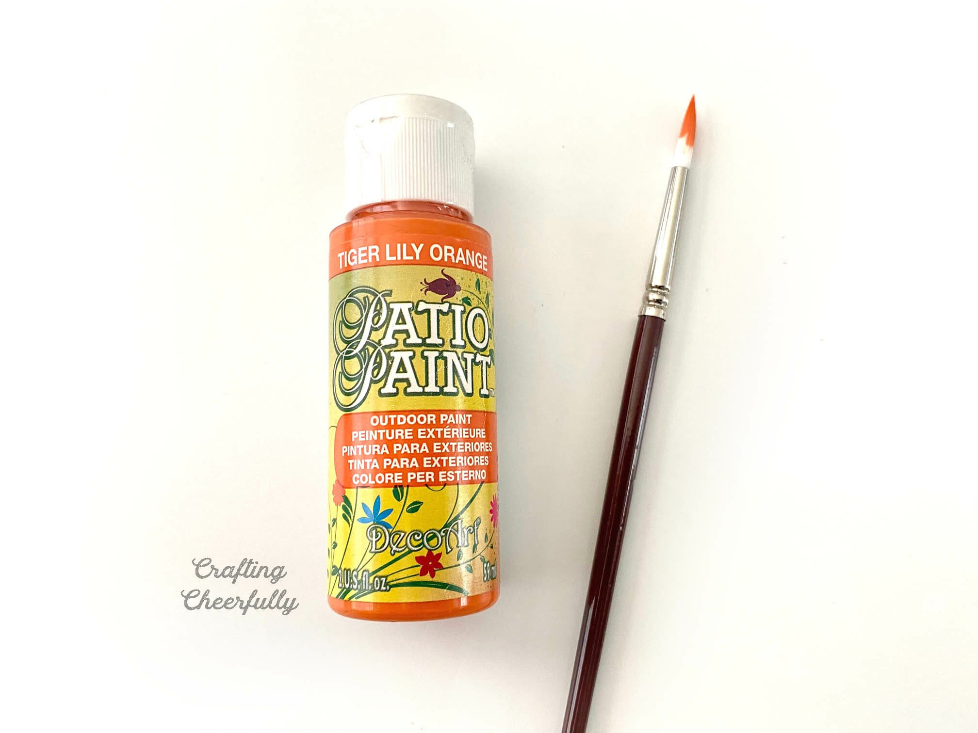 A tube of orange paint lays next to a paint brush with orange paint on the tip.