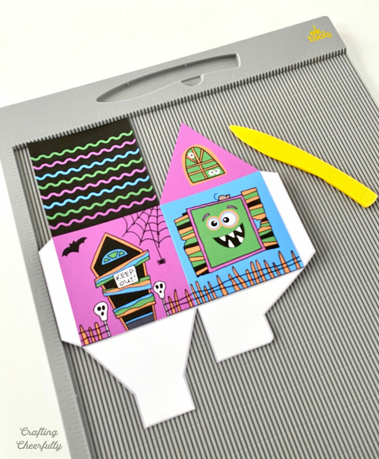 Printable monster box lays on a gray scoring board with a yellow scoring tool.