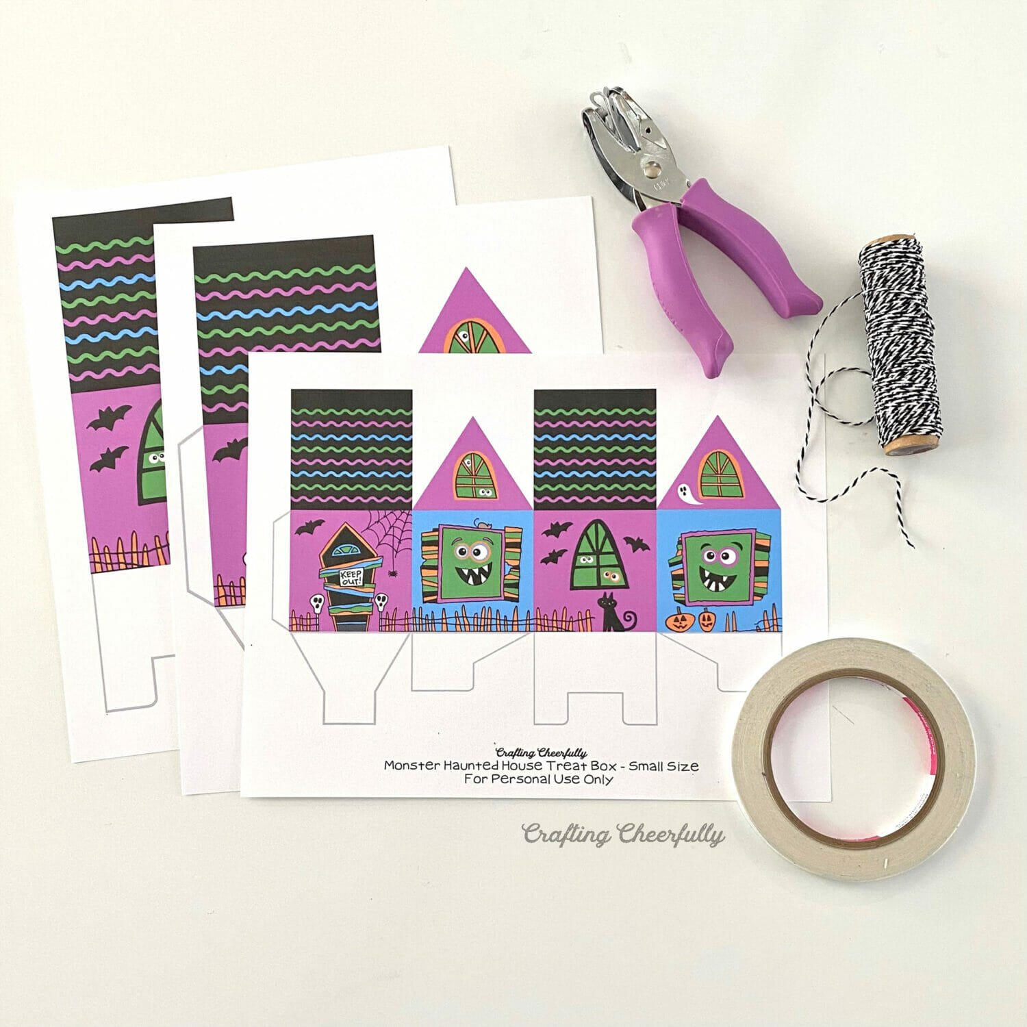 Printable box pages lay next to a hole punch, Baker's twine and a roll of double-sided tape.