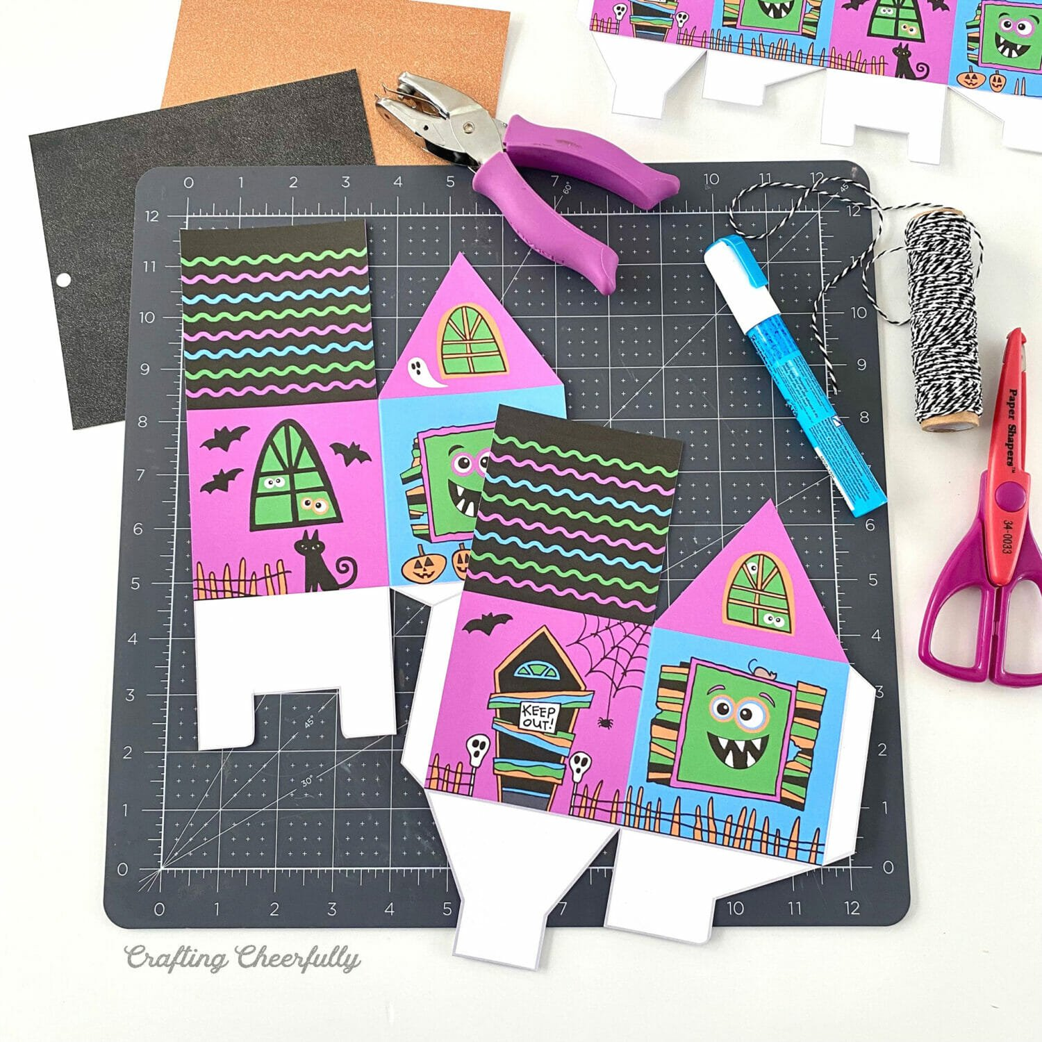 A black cutting mat with the printable halloween monster boxes lays on a white table with craft supplies all around.