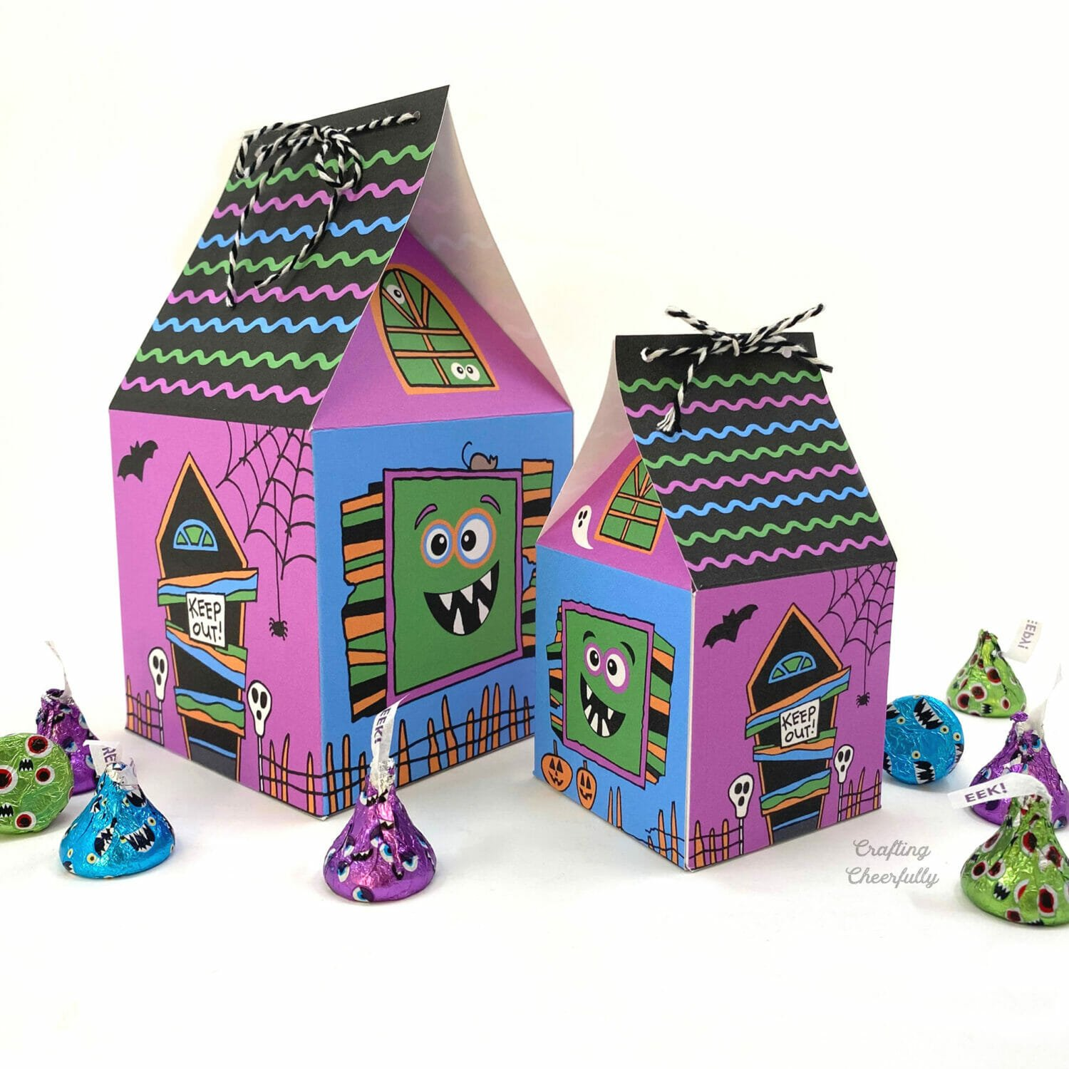 Halloween monster treat boxes sit on a white table with candy around them.