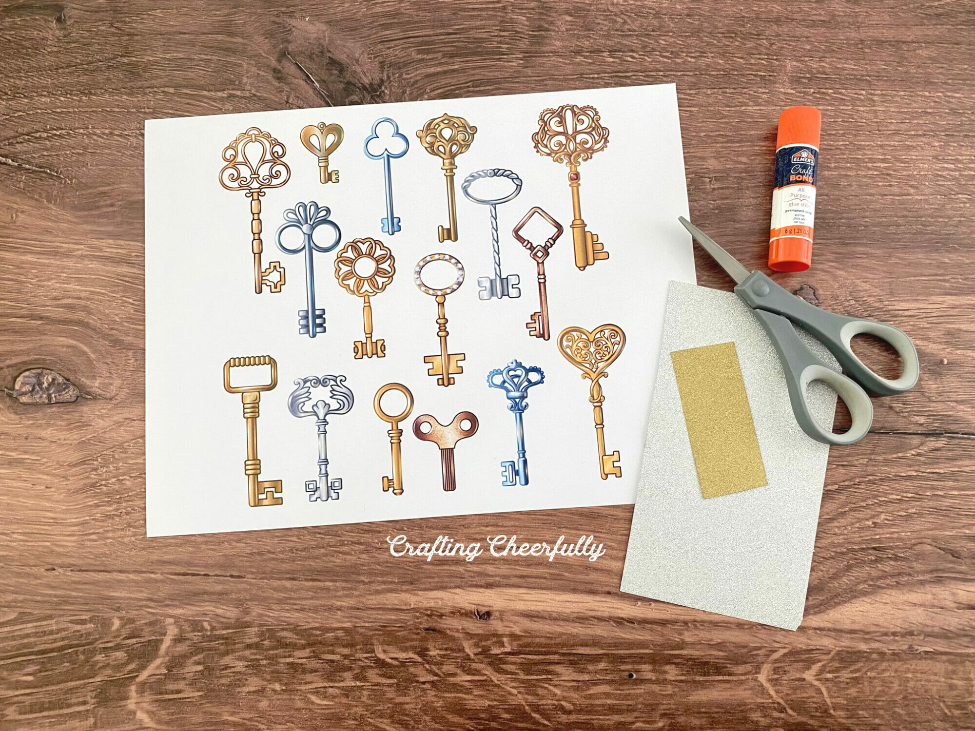 A sheet of printable keys lays next to a scissors, glue stick and glitter paper.