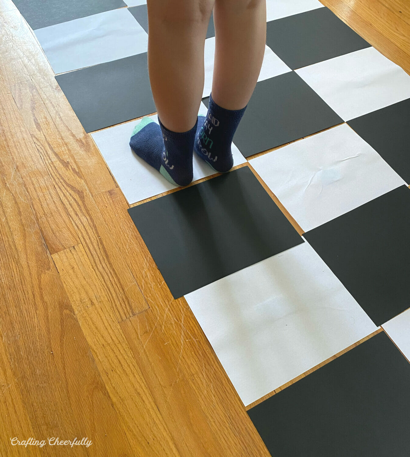 A child stands on sheets of paper laid out to look like a chessboard on the floor.