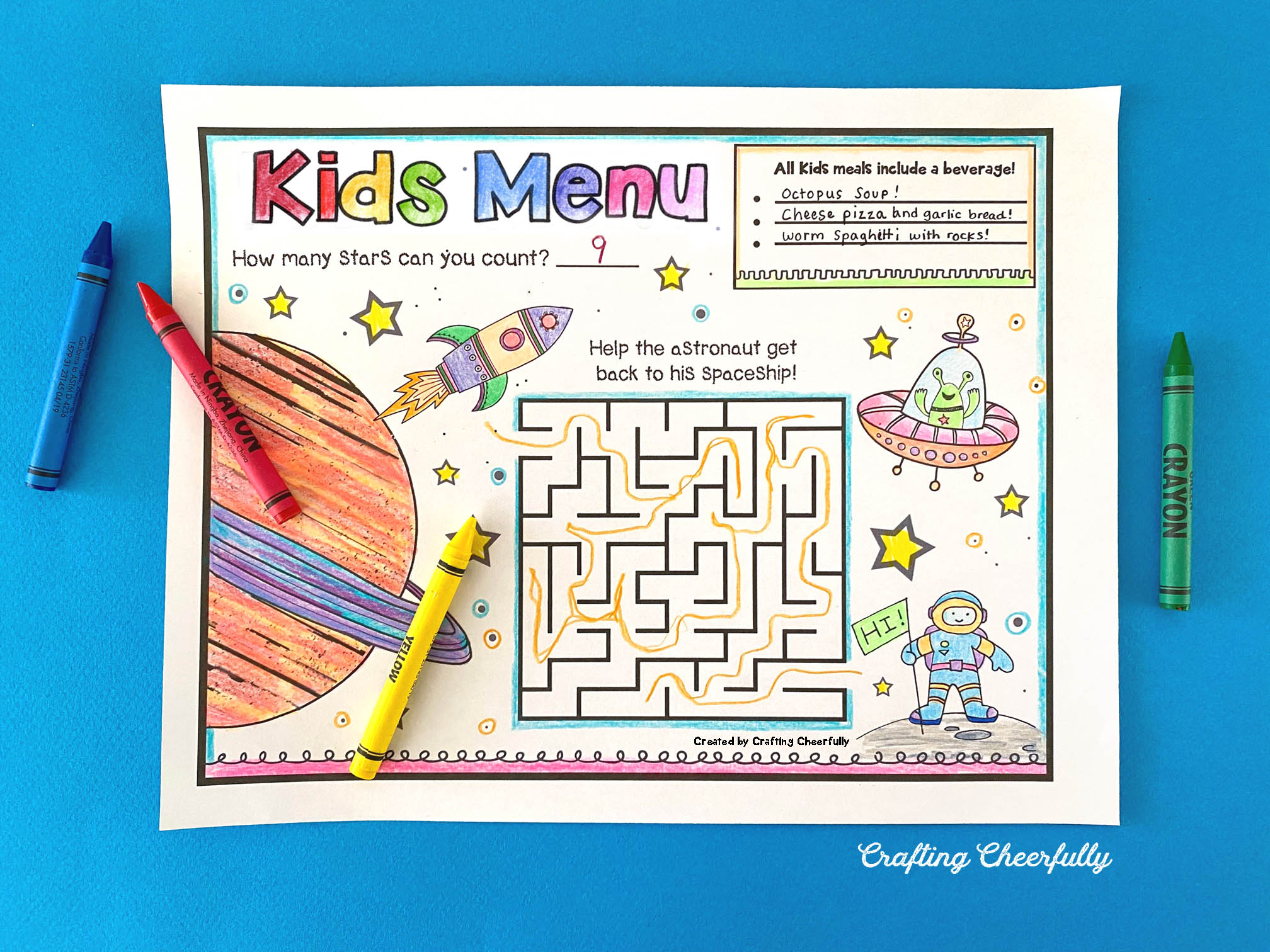 Printable kids menu with fun activities sits on a blue table with crayons.